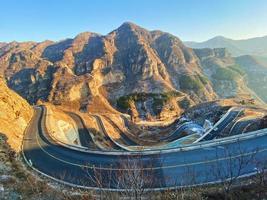 vista della strada di montagna che conduce a una valle foto