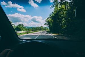 strada, alberi e cielo blu nuvoloso visti attraverso il parabrezza dell'auto foto