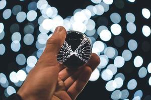persona in possesso di palla d'argento con sfondo bokeh di fondo