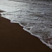 schiuma di mare sulla spiaggia foto