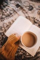 persona che tiene la tazza con il libro aperto
