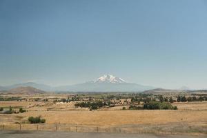 campo in erba e montagna sotto il cielo blu foto