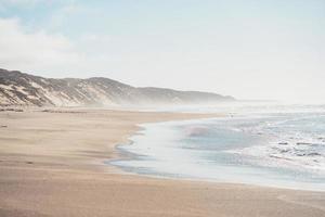 spiaggia nebbiosa durante il giorno foto