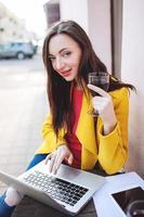 donna con tavoletta di vino rosso e laptop in street cafe foto