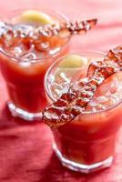 due bicchieri di bloody mary con fette di pancetta
