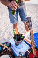 uomo che apre una bottiglia di birra sulla spiaggia. foto