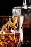 frammento di un bicchiere di whisky con ghiaccio foto