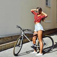 ragazza con una bicicletta in estate foto