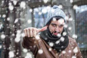 uomo sorridente della barba che fa colpi in nevicata
