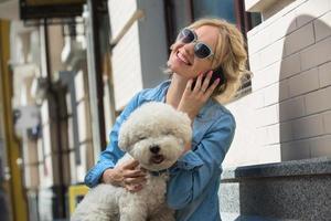 carina bionda con cane bianco bichon frise foto