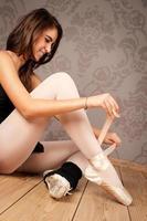 ballerina che lega le sue scarpette da ballo foto