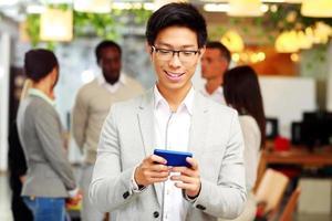 ritratto di un uomo d'affari felice utilizzando smartphone foto