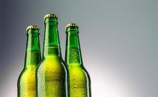 primo piano di tre bottiglie di birra verde collo foto
