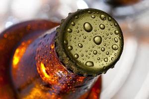 Close up del tappo della bottiglia di birra ricoperta di condensa foto