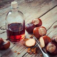 castagne, coltello e bottiglia con tintura su tavola di legno, herba foto