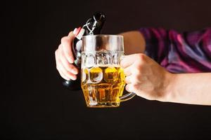 giovane che versa birra dalla bottiglia nella tazza foto