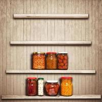 conserve di carote, pomodori, aglio, peperoncino, fagioli su uno scaffale vicino a foto