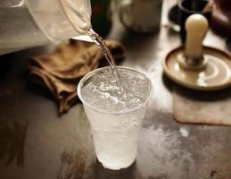 versando acqua fresca in un bicchiere di ghiaccio foto