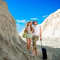 giovane coppia che viaggia in località sabbiosa con i loro bagagli
