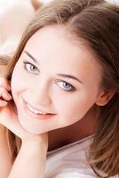 attraente, giovane ragazza puntellando il suo letto. foto