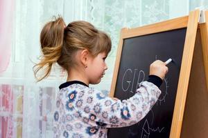 piccola bella ragazza disegno su una lavagna. foto
