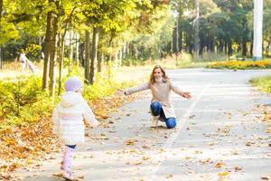 madre di famiglia felice e piccola figlia che giocano sulla passeggiata autunnale foto