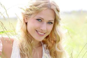 sorridente donna bionda in mezzo al prato