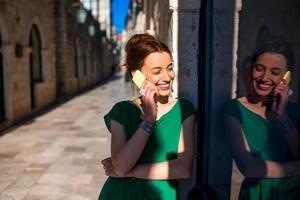 donna con il telefono cellulare nella vecchia via della città foto