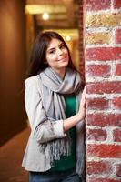 donna felice in piedi vicino al muro di mattoni foto