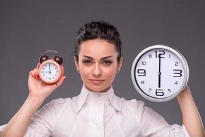 Ritratto di una bella ragazza con grande orologio nelle sue mani foto