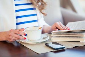 bella ragazza in caffè all'aperto leggendo un libro e
