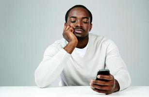 pensieroso uomo africano utilizza lo smartphone foto