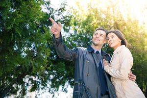 uomo sorridente che punta su qualcosa alla sua ragazza foto