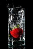 la fragola cade in un bicchiere d'acqua