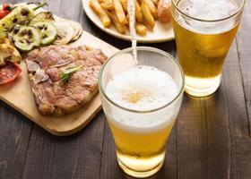 birra che viene versata nel bicchiere con bistecca e patatine fritte foto