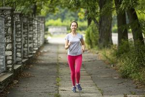 ragazza giovane pareggiatore che corre lungo il sentiero nel parco. foto