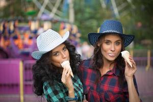 due belle ragazze in cappelli da cowboy che mangiano il gelato