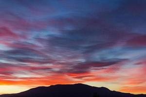 nuvole colorate al tramonto sulla montagna foto