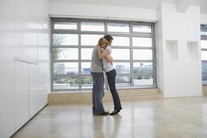 coppia che abbraccia in appartamento vuoto