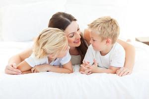 bambini allegri e la loro mamma discutono sdraiati su un letto foto
