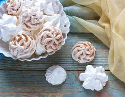 biscotti di meringa bianca su uno sfondo di legno foto