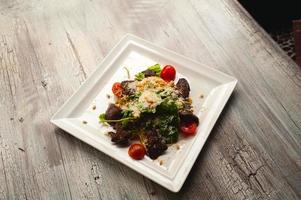 insalata caesar con carne, foglie e pomodori sul piatto bianco