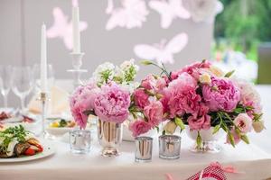 bellissimo bouquet luminoso di peonia sul tavolo di nozze foto