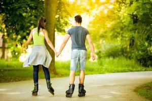 coppia ride rollerblades nel parco