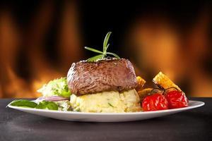 bistecca di manzo fresca su pietra nera e fuoco