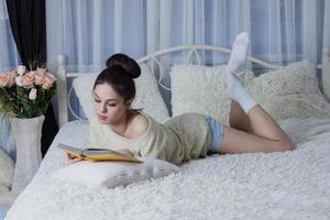 bruna con un libro in camera foto