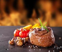 bistecca di manzo fresca su pietra nera e fuoco foto