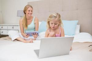 carina bambina con la madre utilizzando tablet e laptop foto