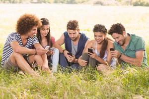 amici felici nel parco che usano i loro telefoni