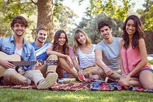 amici felici in un parco che hanno picnic foto